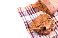 Fresh sliced homemade brown bread with cereals on a kitchen towel. Isolated over white Royalty Free Stock Photography