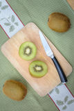 Fresh sliced kiwi fruit and knife. On cutting board Royalty Free Stock Image