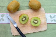 Fresh sliced kiwi fruit and knife. On cutting board Stock Images
