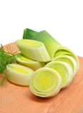 Fresh sliced leeks and dill on a wooden board Royalty Free Stock Photos