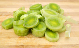 Fresh sliced leeks. And dill on a wooden board isolated on white Stock Photos