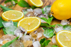 Fresh sliced lemon, bright green mint and ice on a wooden table. A non-alcoholic Mojito cocktail ingridients. Refreshment concept.  Stock Photos
