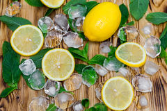 Fresh sliced lemon, bright green mint and ice on a wooden table. A non-alcoholic Mojito cocktail ingridients. Refreshment concept.  Stock Image