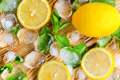 Fresh sliced lemon, bright green mint and ice on a wooden table. A non-alcoholic Mojito cocktail ingridients. Refreshment concept.  Stock Photography