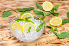 Fresh sliced lemon, bright green mint leaves and frozen ice cubes in a transparent bowl on a wooden table.  Royalty Free Stock Photo