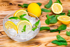 Fresh sliced lemon, bright green mint leaves and frozen ice cubes in a transparent bowl on a wooden table.  Stock Images