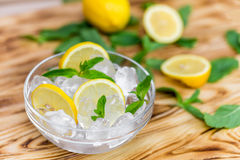 Fresh sliced lemon, bright green mint leaves and frozen ice cubes in a transparent bowl on a wooden table.  Stock Photos