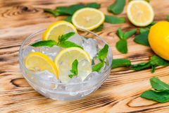 Fresh sliced lemon, bright green mint leaves and frozen ice cubes in a transparent bowl on a wooden table Royalty Free Stock Images