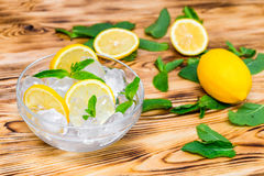Fresh sliced lemon, bright green mint leaves and frozen ice cubes in a transparent bowl on a wooden table Stock Photography