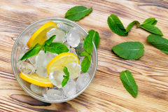 Fresh sliced lemon, bright green mint leaves and frozen ice cubes in a transparent bowl on a wooden table. View from above Stock Photo