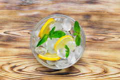 Fresh sliced lemon, bright green mint leaves and frozen ice cubes in a transparent bowl on a wooden table. View from above Stock Images