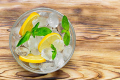 Fresh sliced lemon, bright green mint leaves and frozen ice cubes in a transparent bowl on a wooden table. View from above. Place for text Stock Photo