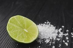 Fresh sliced lime and salt on a wooden table closeup. half lime with salt. appetizer for tequila. Fresh sliced lime and salt on a wooden table closeup. half lime royalty free stock photo