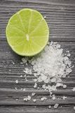 Fresh sliced lime and salt on a wooden table closeup. half lime with salt. appetizer for tequila royalty free stock photo