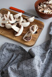 Fresh sliced mushrooms at wooden cutting board. Chopping food ingredients Stock Photo