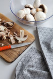 Fresh sliced mushrooms at wooden cutting board. Chopping food ingredients. Stock Images