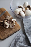 Fresh sliced mushrooms at wooden cutting board. Chopping food ingredients. Food background of fresh champignons Royalty Free Stock Images