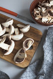 Fresh sliced mushrooms at wooden cutting board. Chopping food ingredients. Food background of fresh champignons Royalty Free Stock Photography