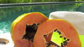 Fresh sliced papaya fruit and a straw hat lie at the pool in the tropical resort.  stock video footage