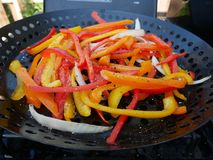 Fresh Sliced Peppers and Onions. On grill stock photo