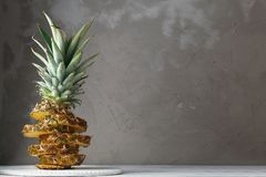 Fresh sliced pineapple on a wooden stand. Over grey concrete background. Copy Space for your text Royalty Free Stock Image