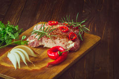 Fresh sliced raw meat on a wooden cutting board. With spices and onions Royalty Free Stock Images