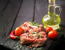 Fresh sliced raw meat on a wooden cutting board. With spices and onions Royalty Free Stock Photos