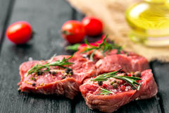 Fresh sliced raw meat on a wooden cutting board. With spices and onions Stock Images