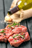 Fresh sliced raw meat on a wooden cutting board. With spices and onions Stock Photos