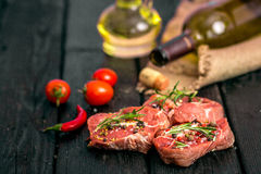 Fresh sliced raw meat on a wooden cutting board. With spices and onions Stock Photo