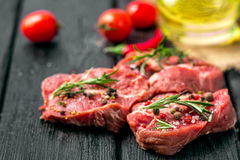 Fresh sliced raw meat on a wooden cutting board. With spices and onions Royalty Free Stock Photo