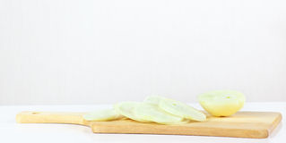Fresh sliced raw onion on a wooden cutting board Stock Images