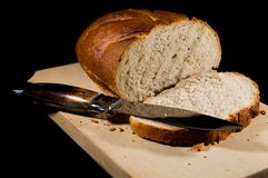 Fresh sliced rye bred with a sharp knife. Isolated on black background Stock Images