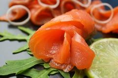 Fresh sliced salmon fillet, lemon and arugula. Closeup royalty free stock photos
