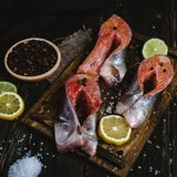 Fresh sliced sea fish with spices and slices of lemon and lime on rustic wooden table Stock Image