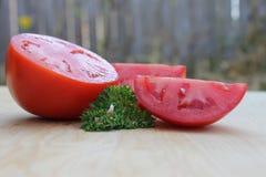 Fresh sliced tomato. Freshly sliced juicy tomato joined with fresh parsley Stock Images