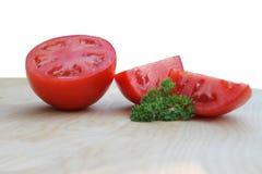 Fresh sliced tomato. Freshly sliced juicy tomato joined with fresh parsley royalty free stock photos
