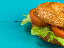 Fresh Sliced Tomato and Lettuce Salad Sesame Seeded Bagel. Tomato and Lettuce Salad Sesame Seeded Bagel Against A Blue Background Stock Photography