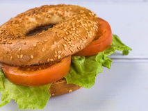 Fresh Sliced Tomato and Lettuce Salad Sesame Seeded Bagel. Tomato and Lettuce Salad Sesame Seeded Bagel Against A Lilac Background Stock Images