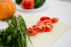 Fresh sliced tomatoe and vegetables on white table in kitchen Stock Images