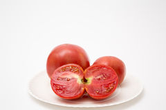 Fresh sliced tomatoes. On paper plate whole tomato homegrown on white stock image