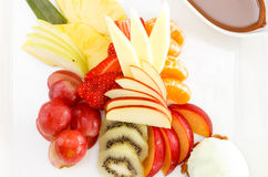 Fresh sliced tropical fruits. Beautiful colourful arrangement of assorted fresh sliced tropical fruits served on a platter for a healthy dessert royalty free stock photo