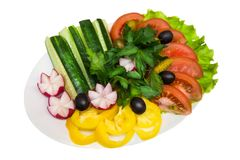 Fresh sliced vegetables on plate on white isolated background. Red tomatoes, yellow peppers, radishes, cucumbers, green salad and parsley. A white plate Royalty Free Stock Photo