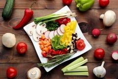 Sliced vegetables in white plate. Fresh sliced vegetables in white plate on wooden table Stock Images