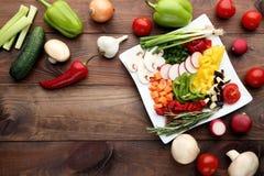 Sliced vegetables in white plate. Fresh sliced vegetables in white plate on wooden table Stock Photography