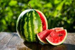 Fresh sliced watermelon wooden background,Ripe striped watermelo. N,Close-up of fresh slices of red watermelon,sweet harvest. Watermelon pattern. Watermelon Royalty Free Stock Image