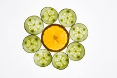 Fresh slices. Photo of some cucumber slices surrounding piece of orange over white background Royalty Free Stock Photography