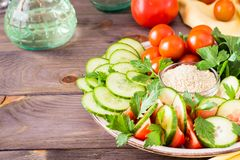 Fresh slices of cucumbers, tomatoes, sesame seeds in a bowl. And parsley leaves on a plate on a wooden table Royalty Free Stock Photos