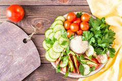 Fresh slices of cucumbers, tomatoes, sesame seeds in a bowl. And parsley leaves on a plate on a wooden table.  Top view Royalty Free Stock Photos