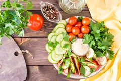 Fresh slices of cucumbers, tomatoes, sesame seeds in a bowl. And parsley leaves on a plate on a wooden table. Oil and seasoning for cooking vegetable salad. Top Royalty Free Stock Images